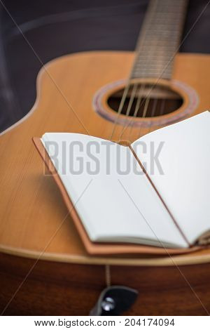 Open journal sitting out six stringed acoustic guitar.