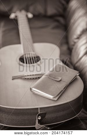 Leather bound journal on a six stringed acoustic guitar.