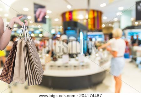 Holding shoping bags by hand on salad bar store blur with bokeh background Miscellaneous Product shelf