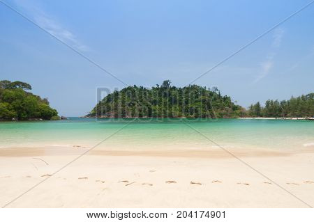 Footprint on white sand and emerald sea .