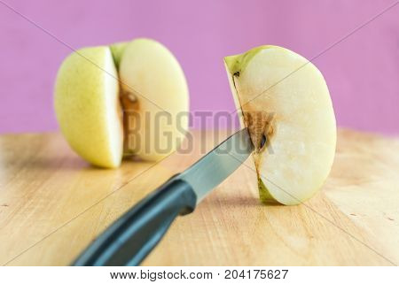 Knife Stabbed Into Chinese Pear Piece On The Wooden Board