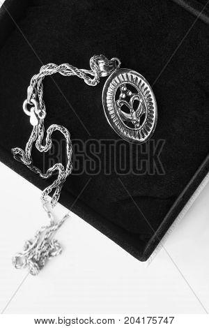 Vintage silver medallion in black jewel box closeup