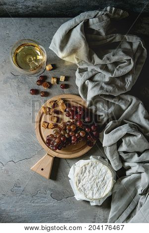 Bunch of red grapes, camembert cheese, croutons and glass of white wine served on wooden serving board over gray kitchen table with textile linen. Rustic style. Top view with space