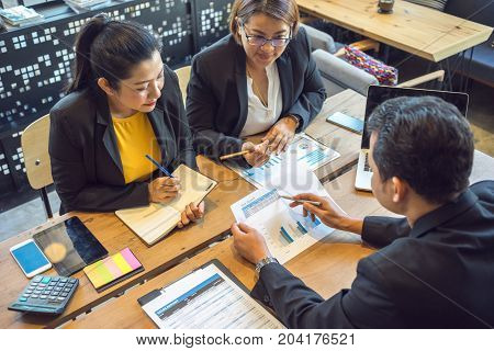 Business consultants is checking and analysis sales figures to plan business strategies with co-worker.