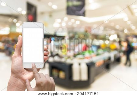 Female hand holding mobile smart phone on salad bar store blur background business concept