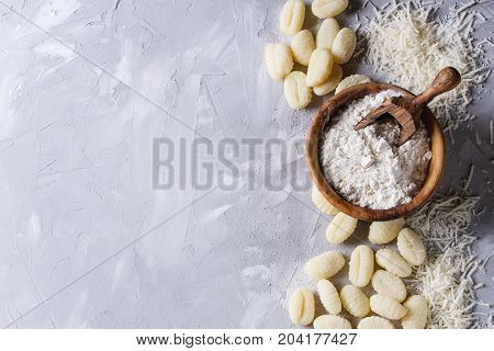 Raw uncooked potato gnocchi with olive wood bowl of flour, grated parmesan cheese over gray concrete background. Top view with copy space. Home cooking.
