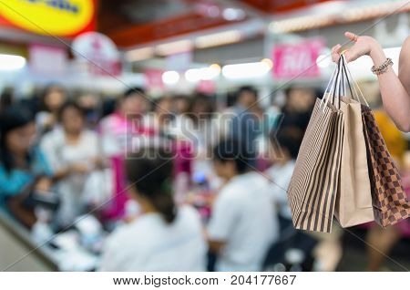 Holding shoping bags by hand on Abstract blurred photo of cashier store blur with bokeh background