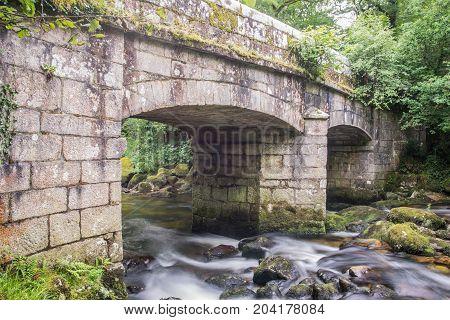 Ancient stone bridge in Shaugh wood, Dartmoor, Devon, UK.