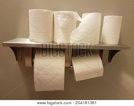 many toilet paper rolls on a shelf in a bathroom stall