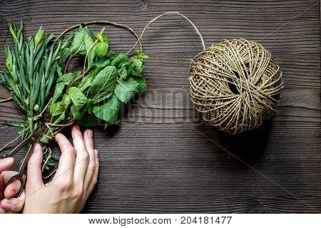 mint and estragon on wooden background with hands top view.