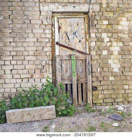 grunge wooden door, cracked brick wall of an abandoned building