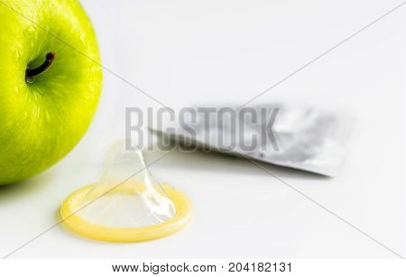 green apple with an open condom on white background. with copy space for text.