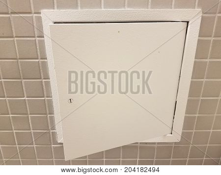 many square grey tiles on a bathroom wall and small door