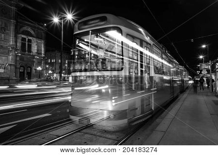 Vienna Austria. Illuminated Opera house in Vienna Austria at night with traffic lights and motion blurred red tram. Black and white
