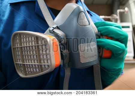 Multi-purpose respirator half mask for toxic gas protection.The man prepare to wear Multi-purpose respirator half mask.