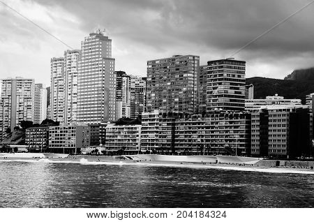 Benidorm Spina. Summer resort Benidorm Spain with beach and famous skyscrapers in the evening. Colorful cloudy sky. Black and white