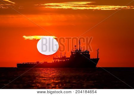 Land of midnight sun. Full sun and orange red sky over tropical Eastern waters of the Orient. Heatwave at sea with fishing boat in silhouette.