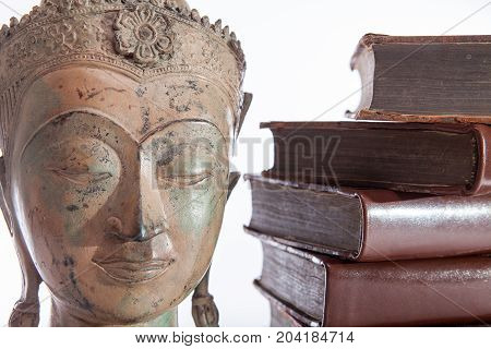Philosophy and ethics. The philosopher Buddha statue and ancient religious education books representing wisdom and philosophical teaching.
