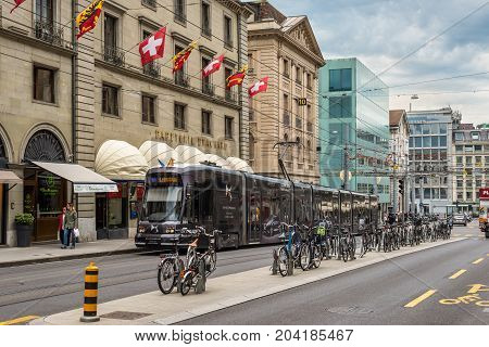 Geneva Switzerland - May 25 2016: Tram bicycles and people on Rue de la Corraterie Street with Swiss flags in the city center Geneva Switzerland.