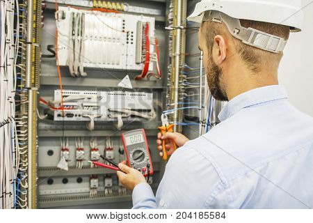 Electrical engineer adjusts control cabinet with multimeter and wire cutters. Testing of electrical automation cabinet by professional.