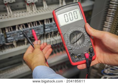 Multimeter in hands of electrician close-up on blurred background of electrical elements. engineer performs adjustment work in control cabinet of industrial equipment.