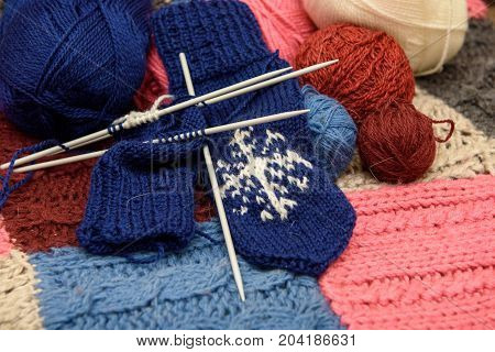 Knitted yarn mittens lie on a woolen blanket.