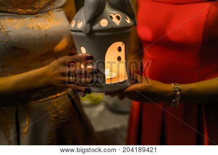 Religious Concept. Two Females Hands Holding A Burning Candle In Candlestick