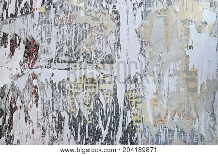 Layers of torn paper peeled posters abstract grunge background texture.