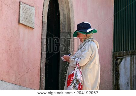 Sintra, Portugal - April 29, 2014: Elderly female tourist taking notes near the old historic building in Sintra, Portugal