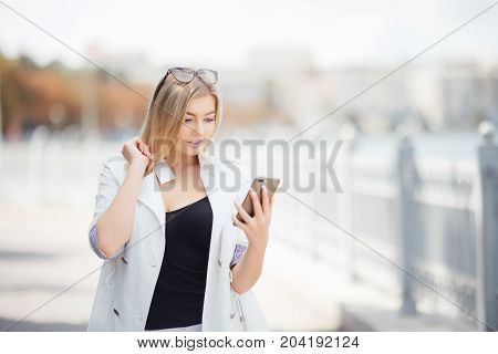 Beautiful Blonde Girl Standing On The Embankment Of The River With The Phone, Reads The Message.