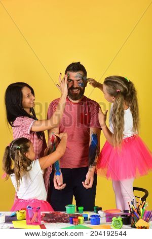 Artists create artwork on guys body. Girls man and woman with happy faces on yellow background copy space. Parents and kids paint on fathers arms and face with gouache. Family time and art concept
