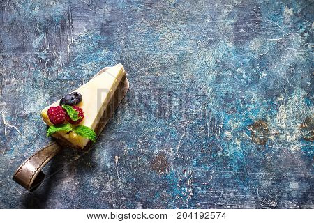 Cheesecake With Berries On Blue Slate Background.