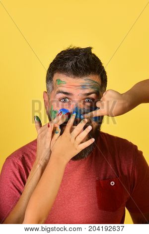 Artists hands paint on guys face. Childrens and female fingers put gouache on bearded mans face. Man with surprised and cheerful face expression on yellow background. Creativity and art concept