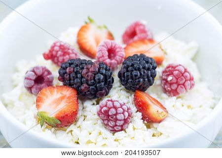 Organic Cottage Cheese With Blackberry, Strawberry And Raspberry In A White Ceramic Bowl On The Kitc