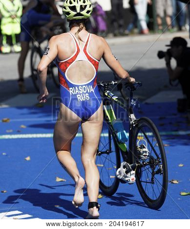 STOCKHOLM - AUG 26 2017: Back of triathlete Valentina Riasova (RUS) running with cycle in the transition zone in the Women's ITU World Triathlon series event August 26 2017 in Stockholm Sweden