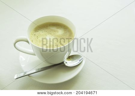 Side view of a cup of cappucino on the white table