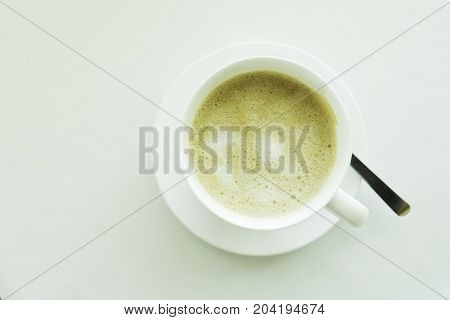 Top view of acup of cappucino on the white table