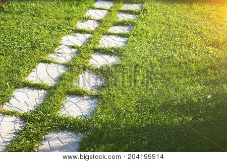 Pathway maden from paving stone in garden with beautiful lawn