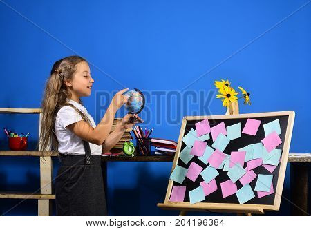 Kid And School Supplies On Blue Wall Background