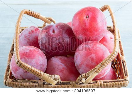 Aprium fruits in a basket over wooden background. Apriums are complex crosses of plums and apricots requiring several generations of crosses to create a new fruit