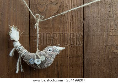 Rustic bird Christmas decoration hanging on twine in front of a dark wood background. Folk art fabric bird decorated with buttons. Natural colors. Copy space.