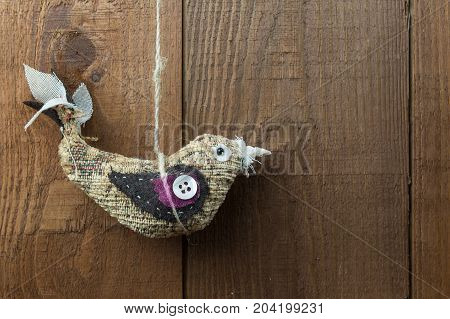 Hanging bird decoration on a wooden background with copy space. Handmade craft bird made in fabric with embellishments hanging from twine.