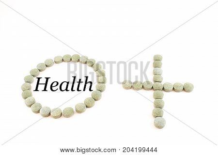 Contour of a circle and the plus sign made up of spirulina pills with word health. Supplement of vitamin B12. White background.