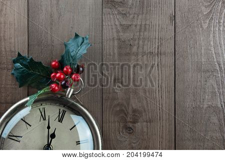 Christmas vintage clock with Holly berries on a wood background. Part of clock showing. Time almost 12 o'clock almost Christmas! Vintage traditional muted neutral brown colors with bright red berries. Lots of copy space.
