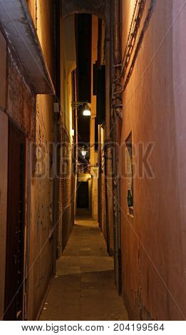 Narrow Venice Street Called Calle In Italian At Night With A Lam