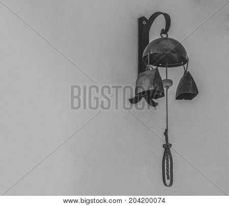 old rustic warning bell cow bell hanging from the white wall in black and white