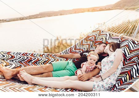 Happy Stylish Family Playing With Cute Daughter And Cuddling, Relaxing In Hammock On Summer Vacation