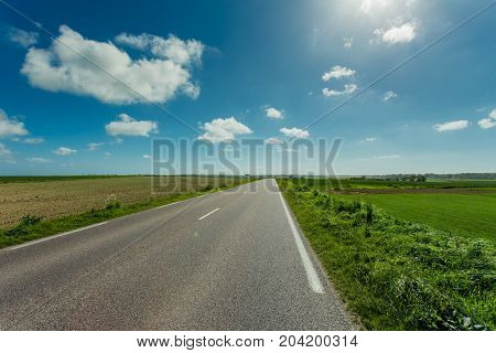 Empty Asphalt Country Road Passing Through Green Agricultural Fields On A Sunny Day In Normandy, Fra
