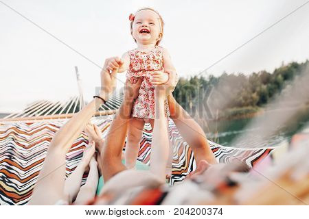 Happy Stylish Family Playing With Joyful Daughter And Cuddling, Relaxing In Hammock On Summer Vacati