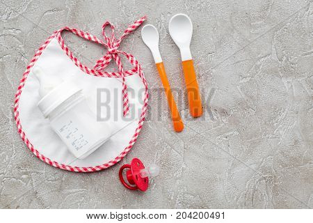 bottle with breastmilk and infant formula powdered healthy food, toys and bib on stone desk background top view mockup